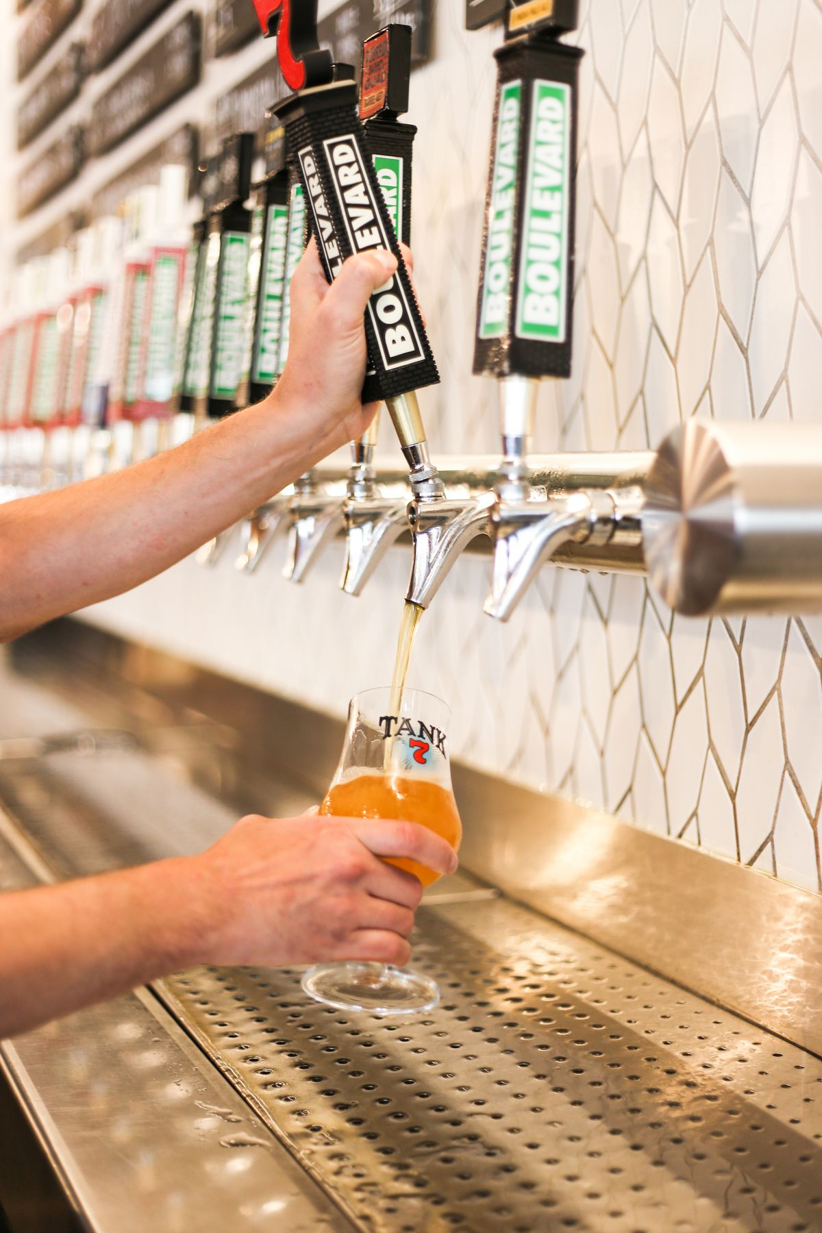 A bartender pours a Boulevard Tank 7 saison from a beer tap handle at a bar.