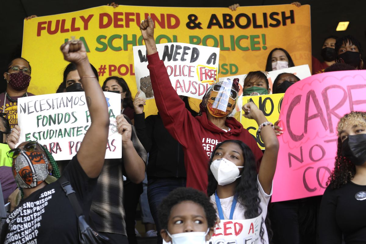 """Several protestors wearing protective masks protest the presence of police in schools. A large yellow sign behind them reads """"FULLY DEFUND & ABOLISH LA SCHOOL POLICE!"""""""