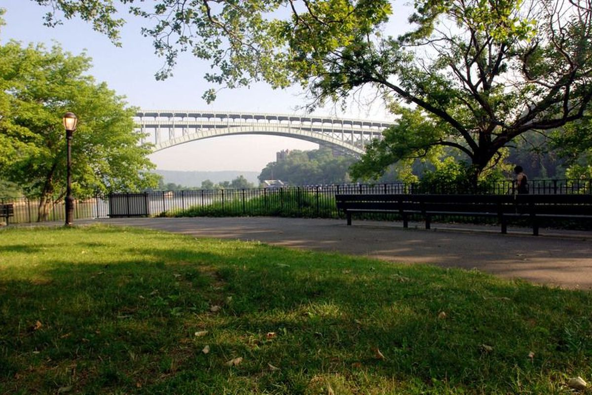A grassy law with a white suspension bridge in the background.