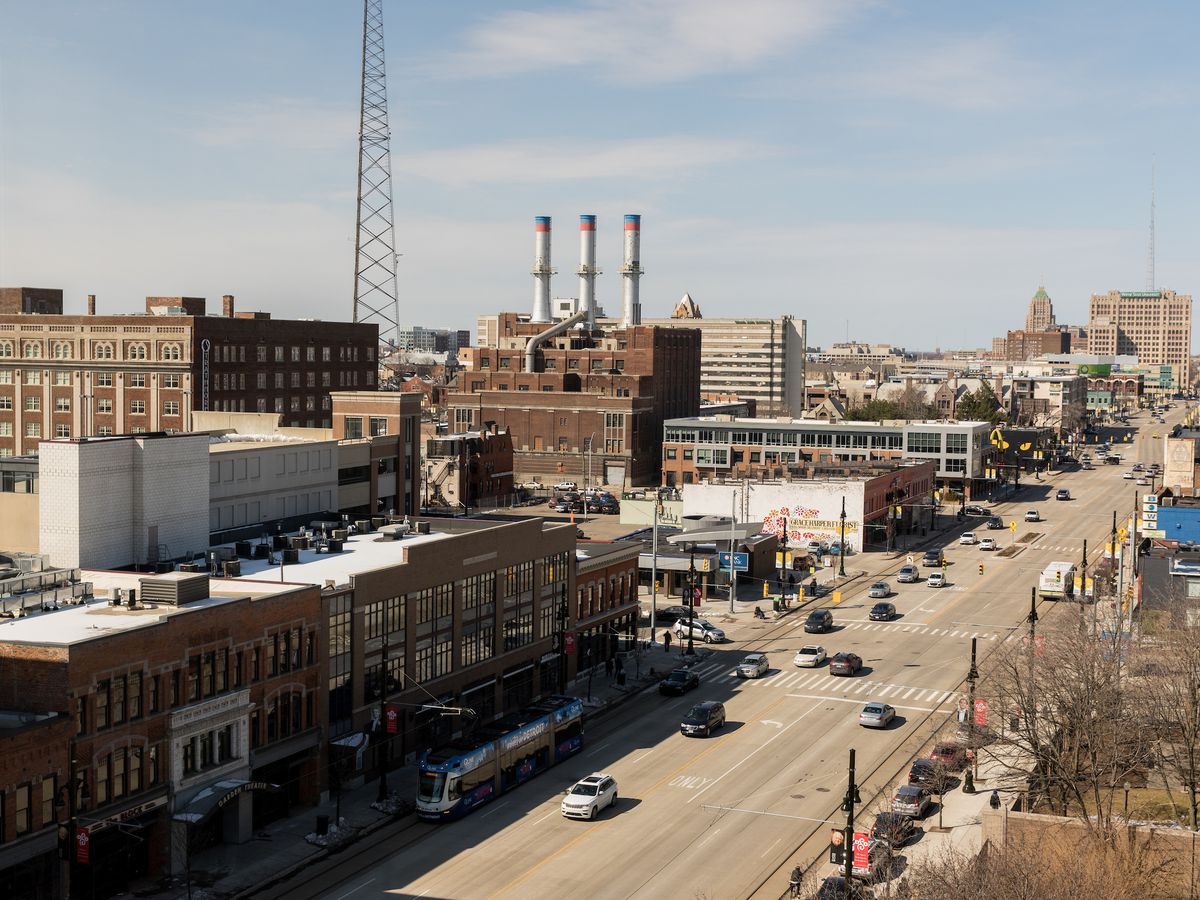 An aerial view of Woodward Avenue in Detroit. Adjacent to a street are buildings and factories.