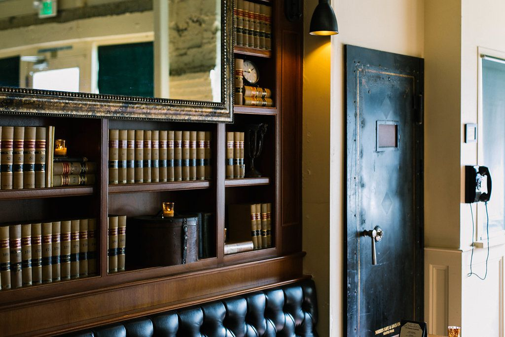 The bank vault door leading to Needle and Thread at Tavern Law, with shelves of books next to it.