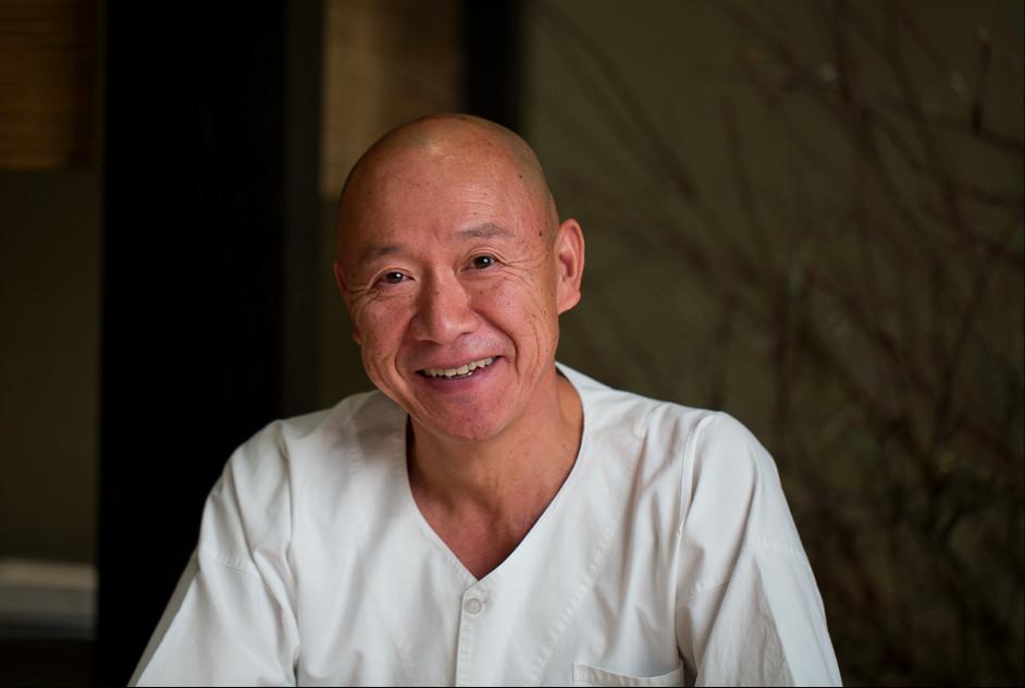 A photo of a smiling Masa Takayama, who is wearing white
