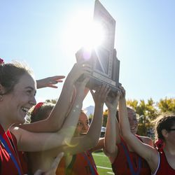 Milford High School's girls cross-country team members hoist their state championship trophy during the 1A State Cross-Country Championships awards ceremony at Sugar House Park and Highland High School in Salt Lake City on Wednesday, Oct. 23, 2019.