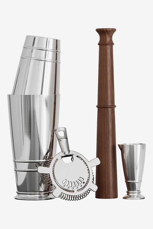 A cocktail shaker, strainer, jigger, and muddler