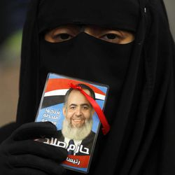 """An Egyptian woman holds a picture of a potential presidential candidate Hazem Abu Ismail, with Arabic writing which reads, """" Hazem Abu Ismail is the President of the Republic."""",  during an support rally outside a courtroom in Cairo, Egypt, Wednesday, April 11, 2012. Abu Ismail is challenging authorities to produce evidence backing their allegations that his mother has a U.S. citizenship, thus disqualifying him from the presidential race."""