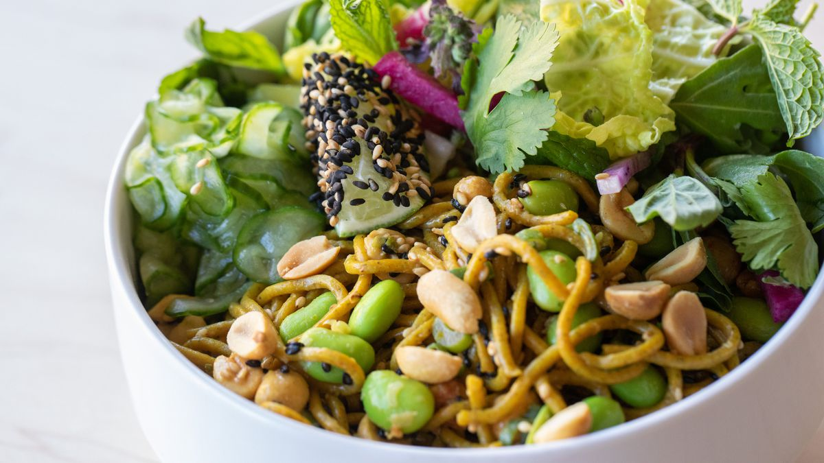 A bowl of noodles tossed with edamame and peanuts, topped with a sesame-seed-coated lime, herbs like cilantro and mint, and shaved cucumbers.