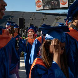 Graduates of Whitney M. Young Magnet High School proceed out of Soldier Field to their friends and families.
