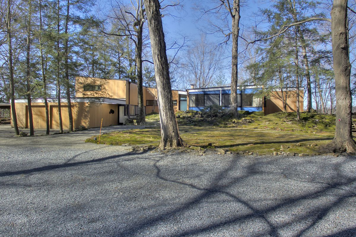 Modern home with wood-frame and siding on private wooded lot.