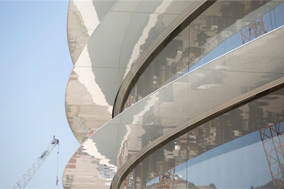 A worker on a crane scales the curved side of the new Apple headquarters, under construction.