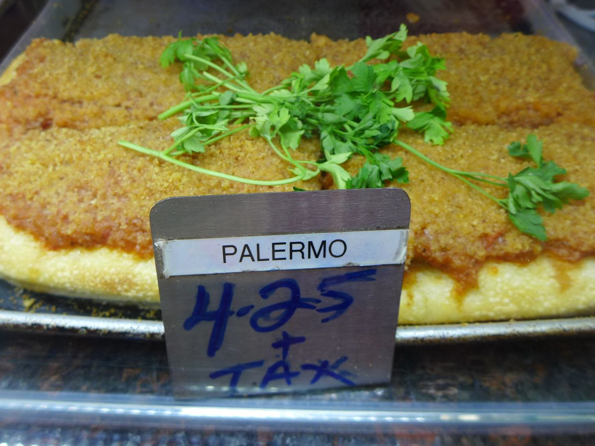 A corner of a square pie with crumbs on top and sprigs of flat leaf parsley.