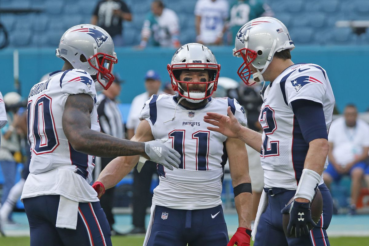 Tom Brady talks with Josh Gordon and Julian Edelman of the New England Patriots prior to the NFL game against the Miami Dolphins on December 9, 2018 at Hard Rock Stadium in Miami Gardens, Florida.