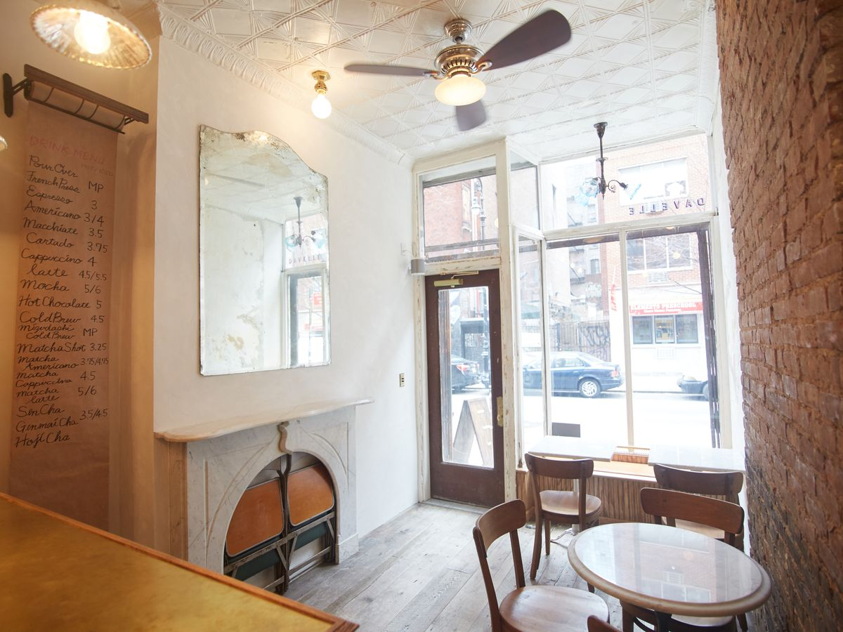 A snug cafe with high ceilings, a mirror, a single table, and a coffee menu written in cursive on paper