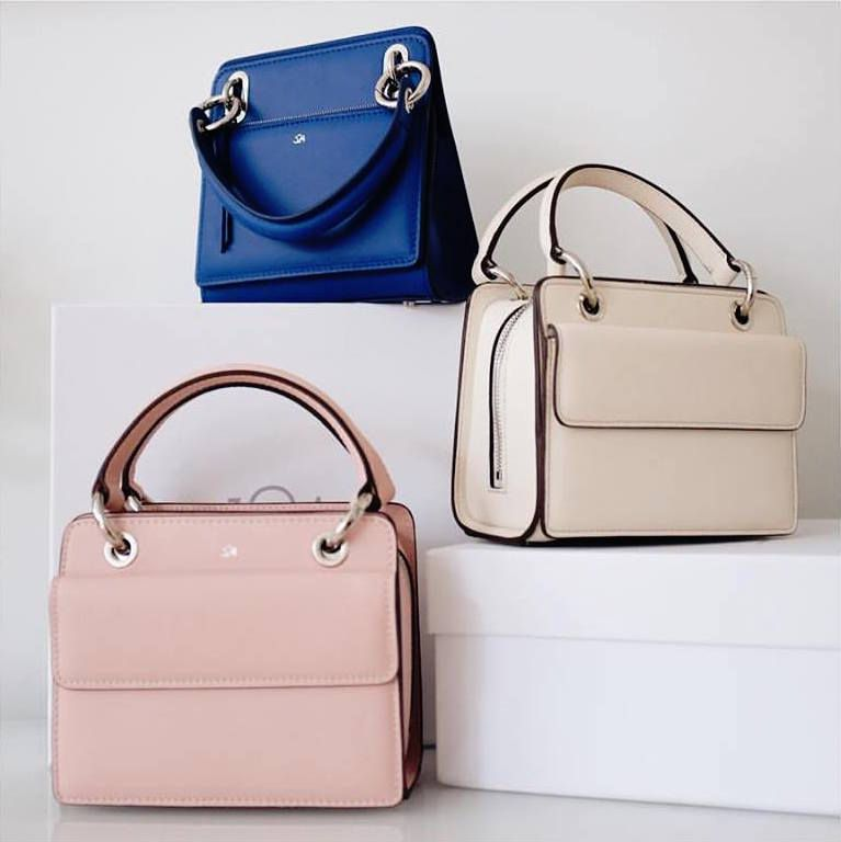 Three handbags in pink, blue, and taupe