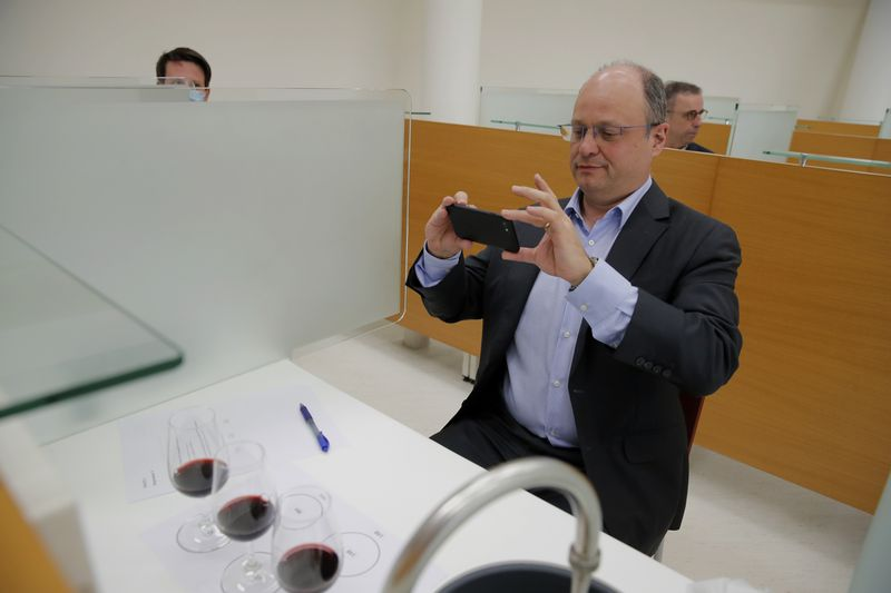 Chief Operating Officer of French National Centre for Space Studies (CNES) Lionel Suchet takes a pictures of glasses of red wine during a tasting of regular bottles and others that spent a year orbiting the world in the International Space Station
