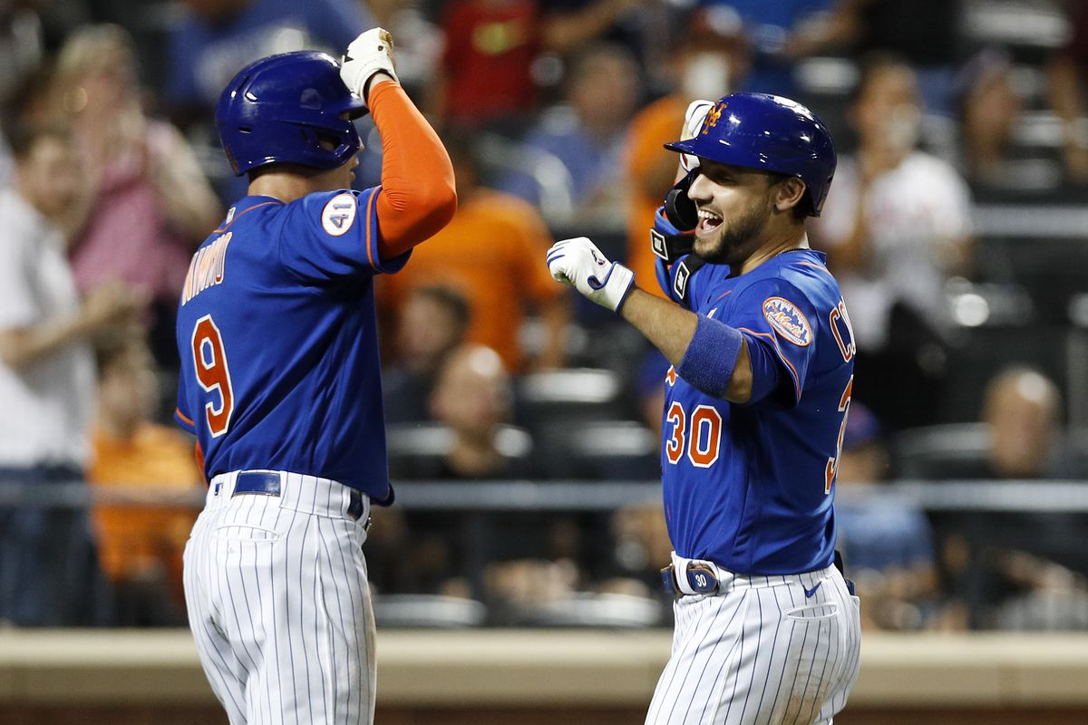Michael Conforto of the New York Mets celebrates his fourth inning two run home run against the Miami Marlins with teammate Brandon Nimmo at Citi Field on August 31, 2021 in New York City.