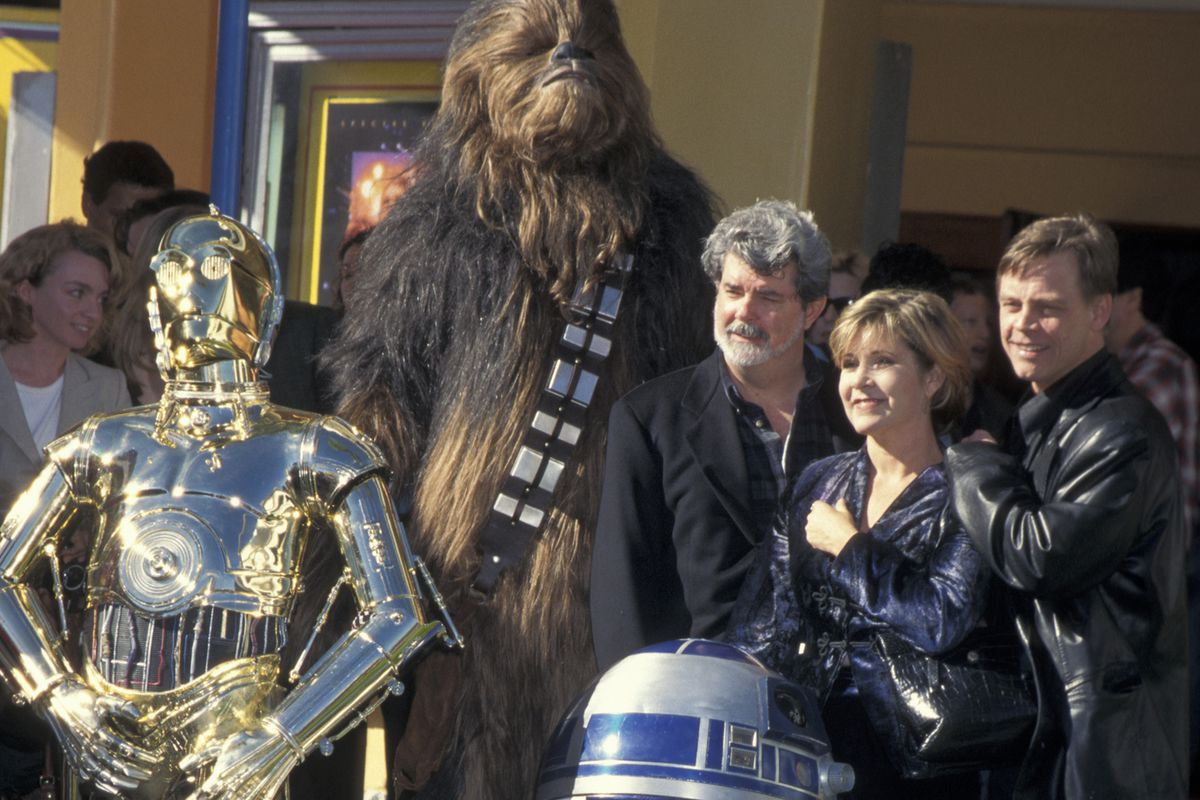 C-3PO, Chewbacca, George Lucas, Carrie Fisher, and Mark Hamill in 1997.