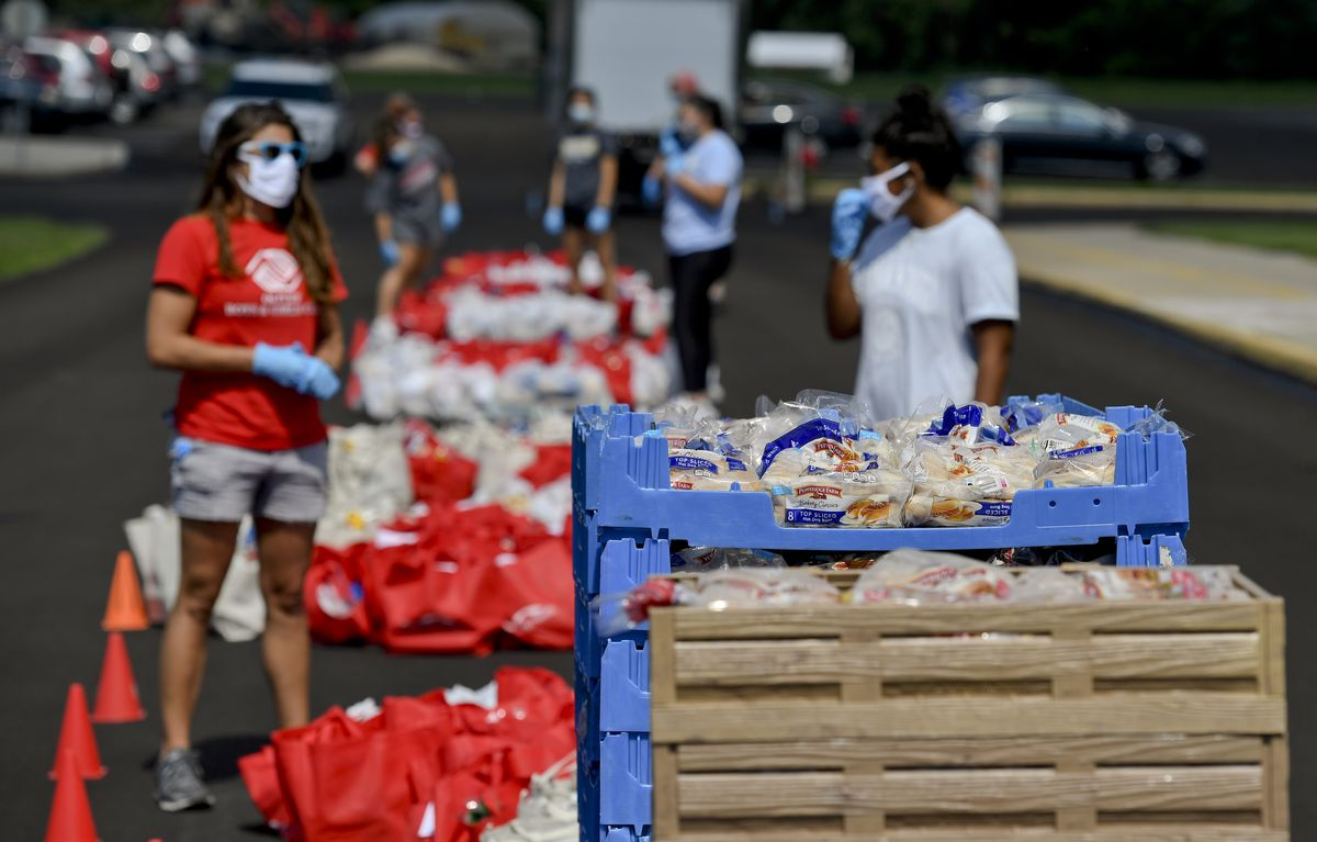 A woman wearing a mask stands alongside crates and reusable bags containing food donations.