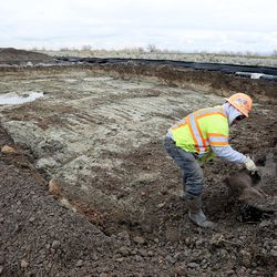 A worker repairs a soft spot in the temporary haul road for the new prison in Salt Lake City on Wednesday, Feb. 22, 2017.