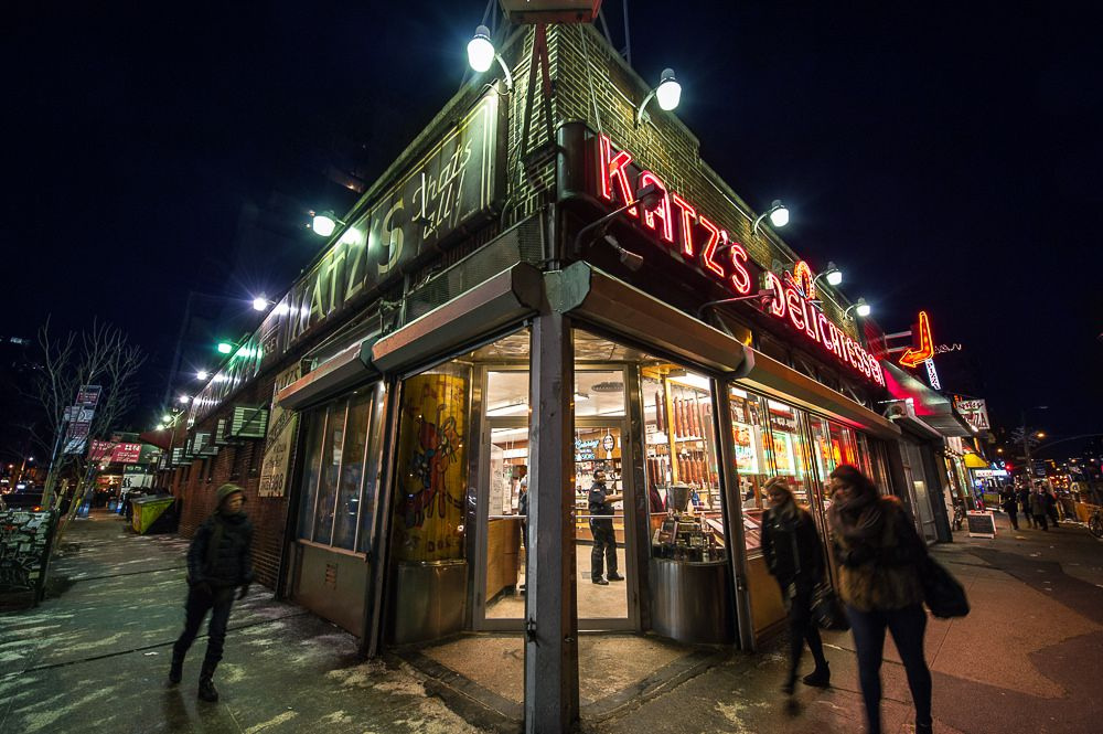 """The front of a sprawling corner store at night, with red neon letters that read """"Katz's Delicatessen"""" in capital letters"""