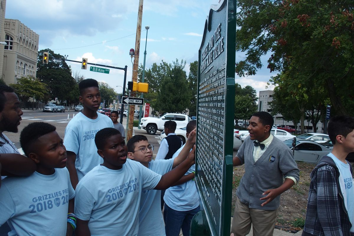Students at Memphis Grizzlies Preparatory Charter School examine a historical marker meant to share a more complete story of Nathan Bedford Forrest, a Confederate general, slave trader, and early leader of the Ku Klux Klan.