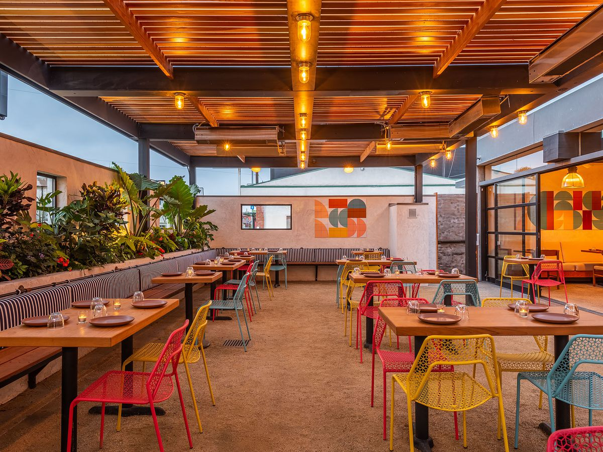 Nueva's outdoor patio covered with pergola and colorful chairs.