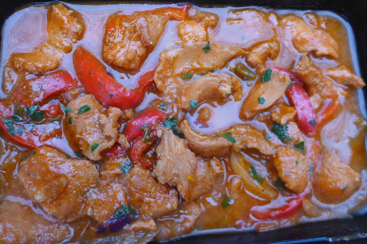 Pieces of white conch and red bell pepper in a red sauce.