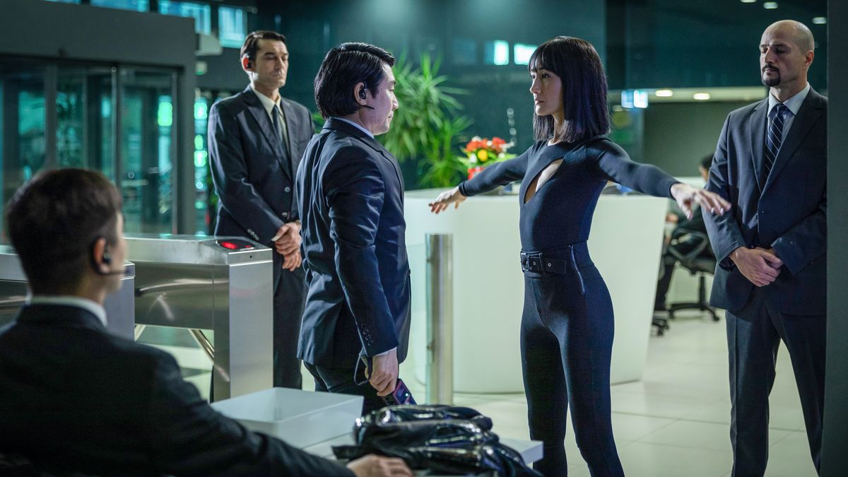 Maggie Q in a skintight black outfit extends her arms to be frisked by a security team in The Protégé