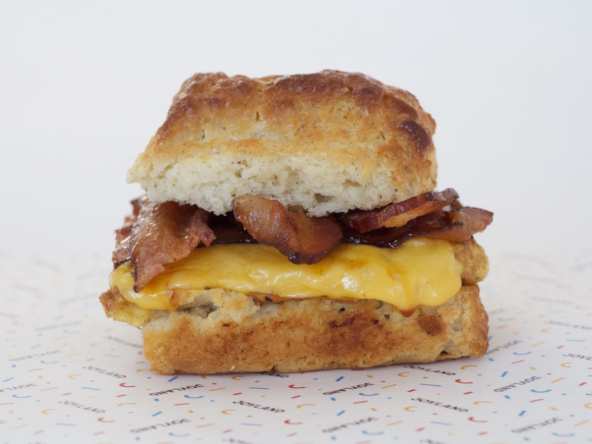 bacon, egg, and cheese biscuit in center of photo, close up, on Joyland printed paper