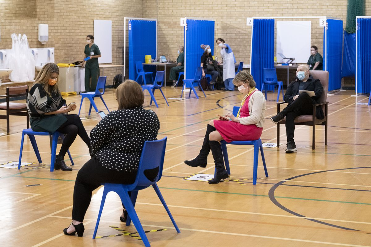 People sitting on chairs spaced well apart on the floor of a gymnasium.