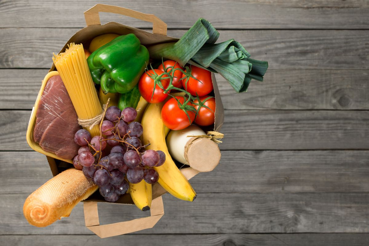 Stock photo of a brown paper bag of groceries on a wooden surface, viewed from overhead