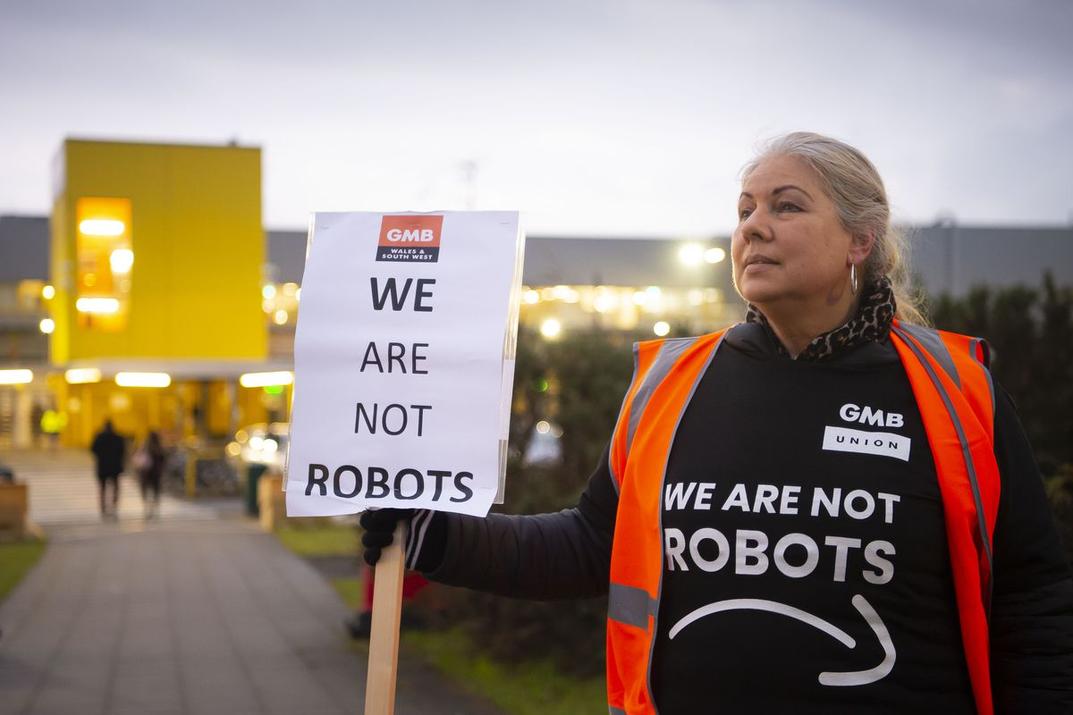 """A person wearing a shirt with an upside-down Amazon logo (a frown instead of a smile) that reads """"We are not robots"""" carries a sign with the same message outside an Amazon fulfillment center."""