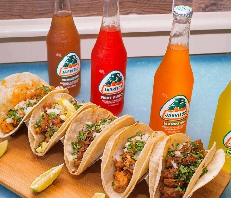A diagonal line of tacos runs parallel to a line of Jarritos sodas in various flavors, colored red, orange, and yellow