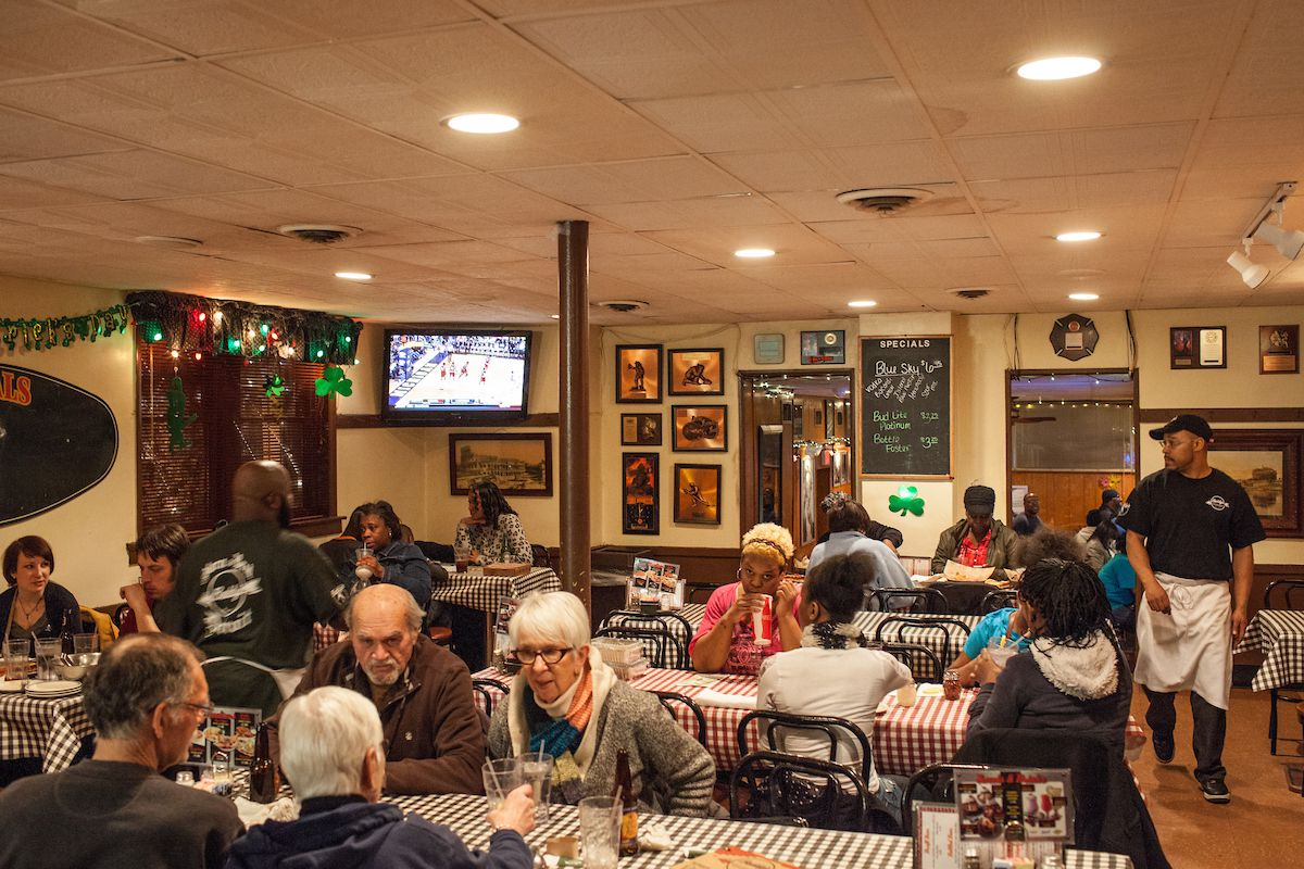 Older customers sit at check tablecloth covered tables below a drop ceiling inside Buddy's Pizza.