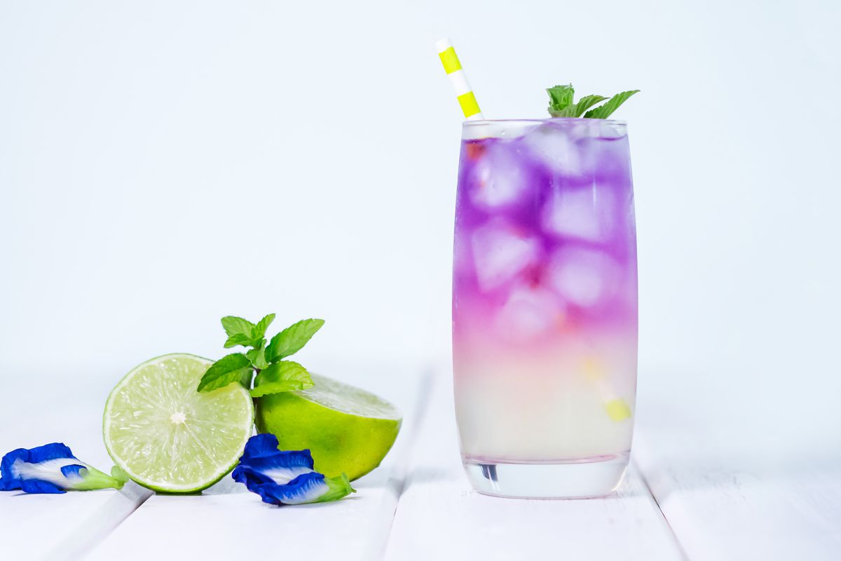 A glass with a purple and yellow iced drink and a yellow straw next to sliced limes and blue flower petals