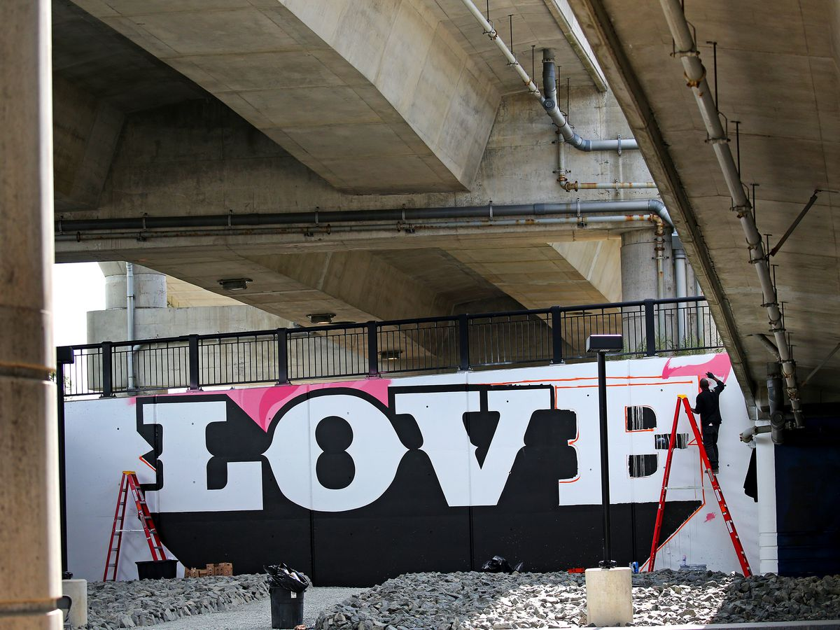 """A park underneath a highway overpass, and """"Love"""" is painted on the overpass."""