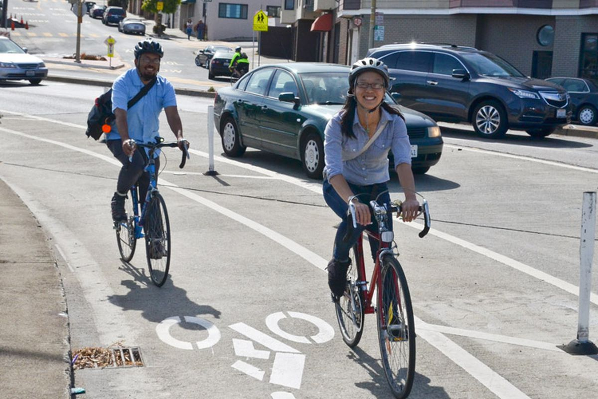 Three people on bikes are riding in a protected bike lane in San Francisco.