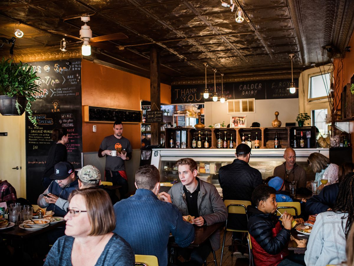 Customers fill tables inside the orange-walled dining room at Mudgie's deli.