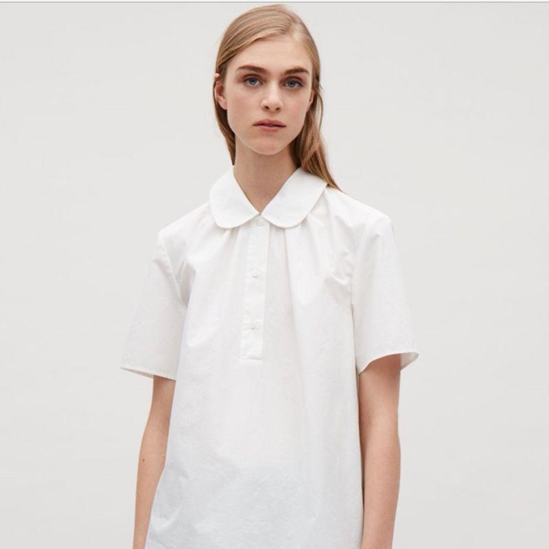 A model wearing a white peter pan collar shirt.