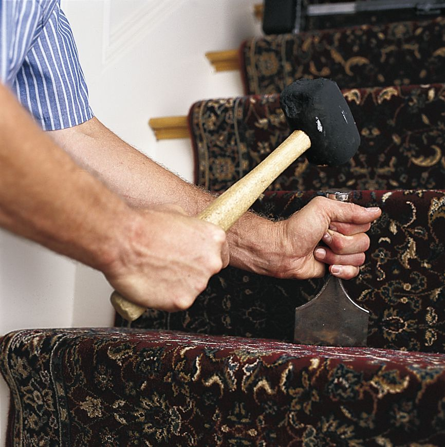 Man Uses Carpet Tool And Rubber Mallet To Pack Stair Runner