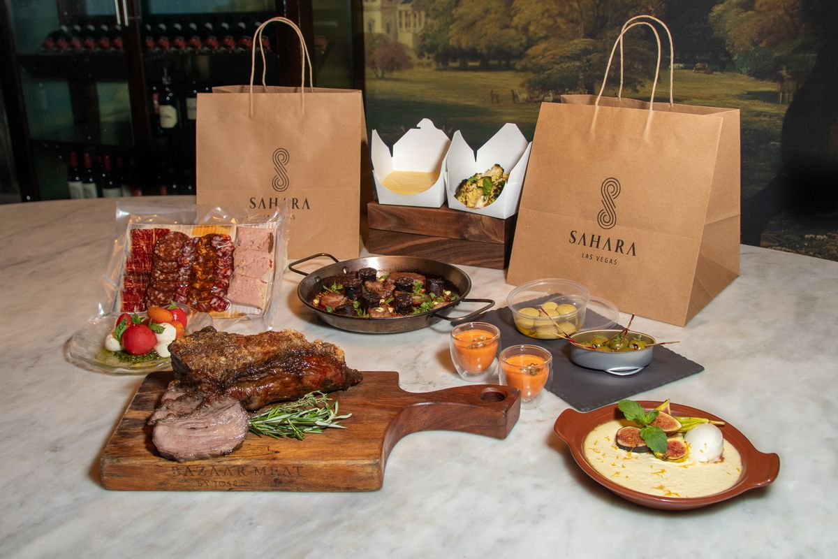 Wagyu beef on a cutting board with sides such as flan, charcuterie, and more