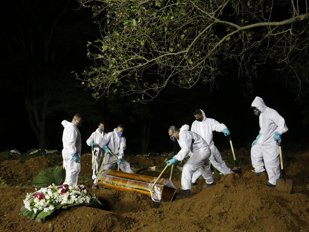 In this March 31, 2021 file photo, cemetery workers work hours past sundown, as they lower the coffin that contain the remains of a COVID-19 victim into a freshly dug grave at the Vila Formosa cemetery in Sao Paulo, Brazil.