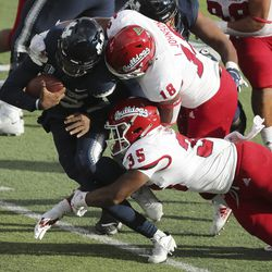 Utah State Aggies quarterback Jason Shelley (15) is tackled by Fresno State Bulldogs linebacker Malachi Langley (35) in Logan on Saturday, Nov. 14, 2020.