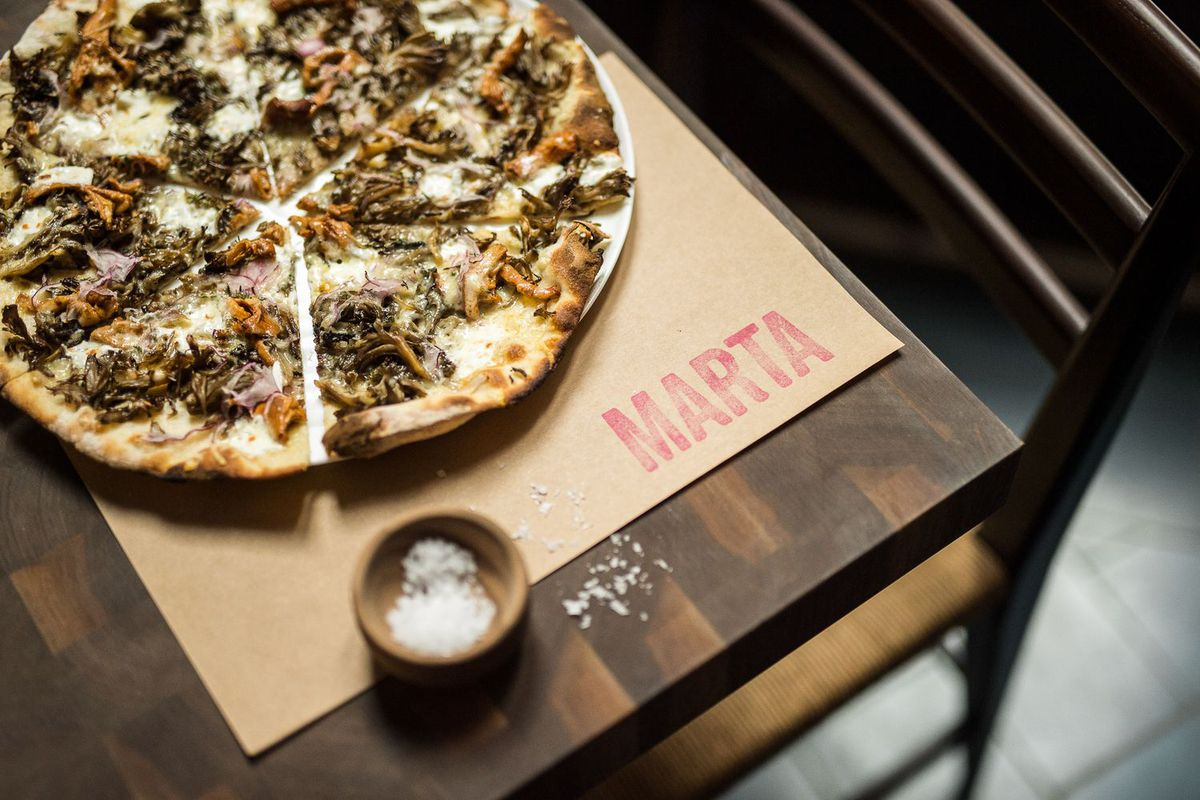 """A pizza on a paper placemat that reads """"Marta"""""""