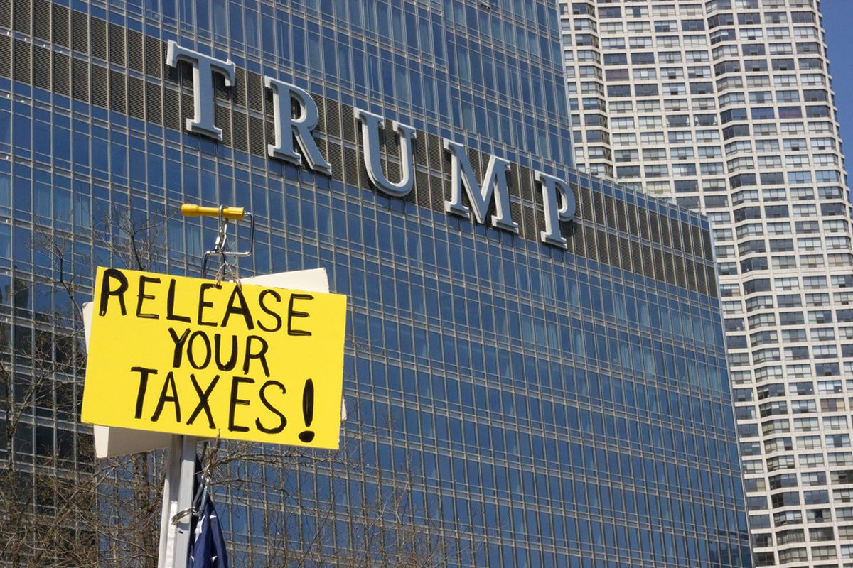 A protester holds a sign across the river from Trump International Hotel and Tower on Saturday.   Matthew Hendrickson/Sun-Times<br>