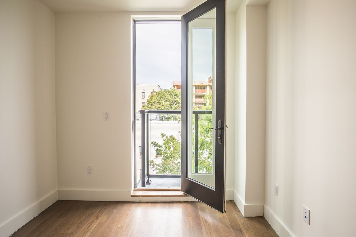 A bedroom with beige walls, hardwood floors, and a glass door that leads to a balcony.