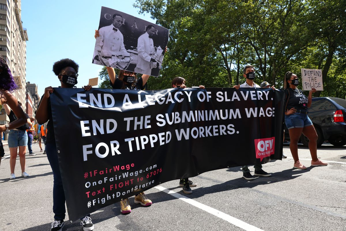 """Members of 1 Fair Wage hold up a banner during a """"Strike for Black Lives"""" rally on July 20, 2020 in New York City."""
