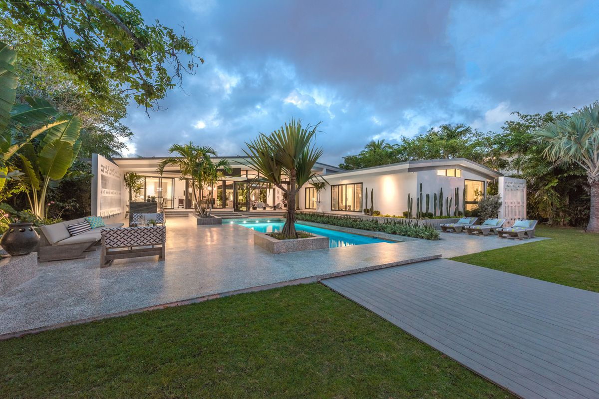 Backyard view of a midcentury modern home in Miami Beach designed by a famous french architect, with large glass windows.
