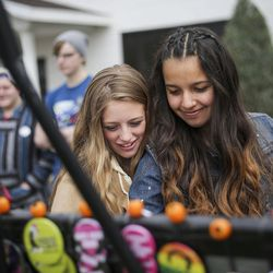 """Tara Lair, left, and McKenzie Patino, right, look at buttons while waiting in line outside the """"Come Together and Fight Back"""" tour with Vermont Sen. Bernie Sanders andDemocratic National Committee Chairman Tom Perez at the Rail Event Center in Salt Lake City on Friday, April 21, 2017."""