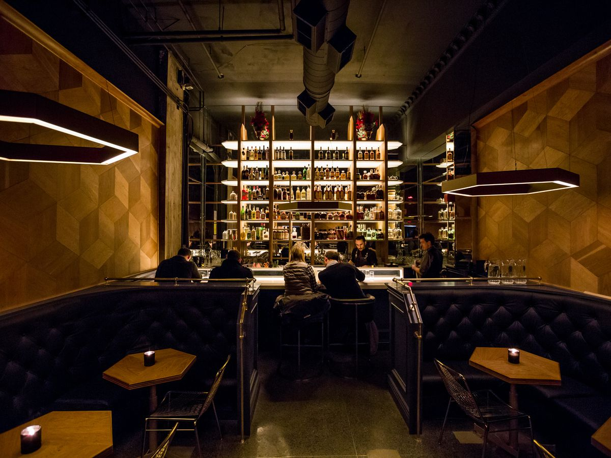 A bar with hexagon shaped lighting and wood paneling as well as hexagon tables.