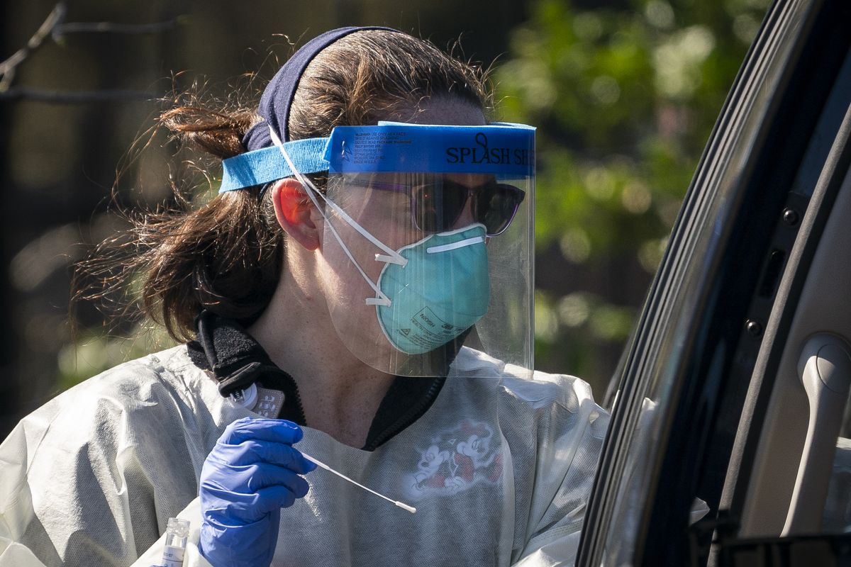 A medical professional from Children's National Hospital administers a coronavirus test at a drive-thru testing site for children in Washington, DC.